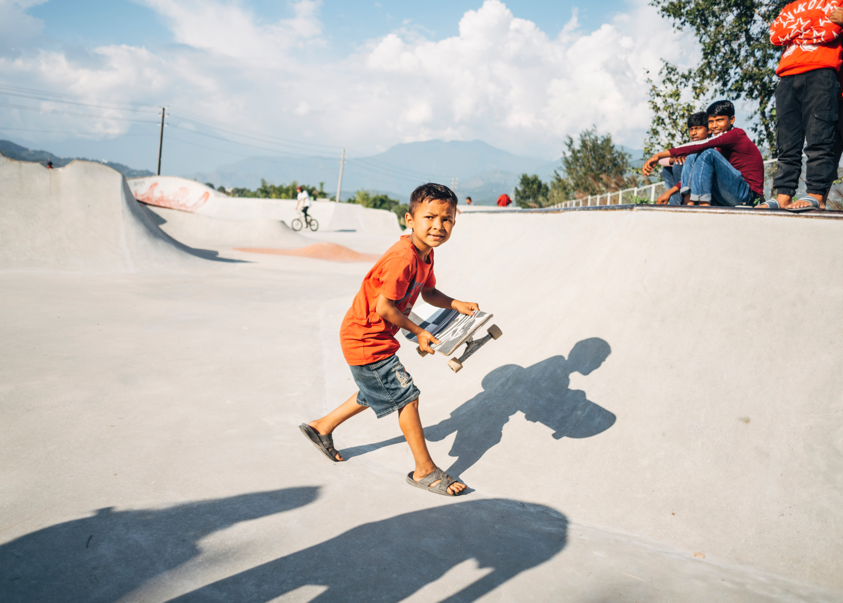 A young child holding a skateboard in a skateboard ramp.