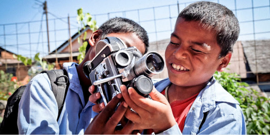 Two children holidng a camera.